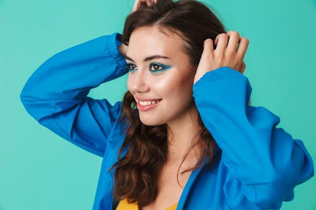 Alegre mulher vestindo capa de chuva ou jaqueta sorrindo e segurando as mãos na cabeça