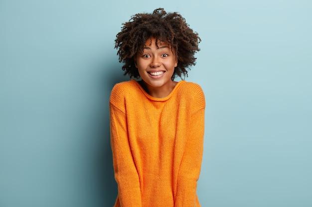 Alegre namorada afro-americana recebe surpresa inesperada do namorado, tem um sorriso largo, sente-se satisfeita, usa um macacão laranja, expressa emoções agradáveis, isolada sobre uma parede azul. expressões faciais