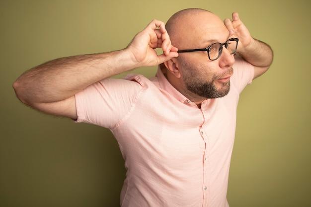 Alegre olhando para o lado de um homem careca de meia-idade, vestindo uma camiseta rosa, usando e segurando óculos isolados na parede verde oliva