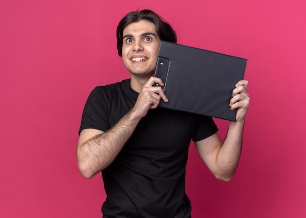 Alegre olhando para um jovem bonito vestindo uma camiseta preta segurando uma prancheta ao redor do rosto isolado na parede rosa