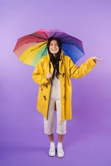Alegre otimista linda mulher morena em capa de chuva amarela posando isolado sobre a parede roxa segurando o guarda-chuva.