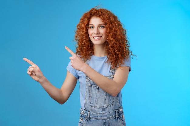 Alegre otimista verão menina ruiva encaracolado penteado usar macacão jeans se preparando férias na praia apontando para o canto superior esquerdo promover loja sorrindo encantado aproveite as férias.