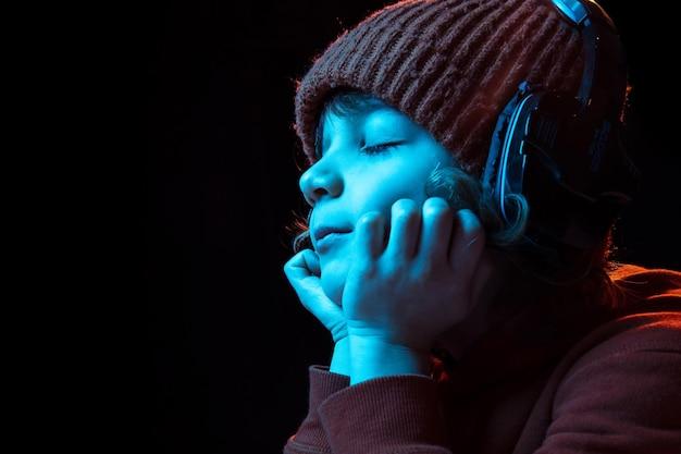 Alegre ouvindo música em fones de ouvido com os olhos fechados. retrato do menino caucasiano em fundo escuro em luz de néon.