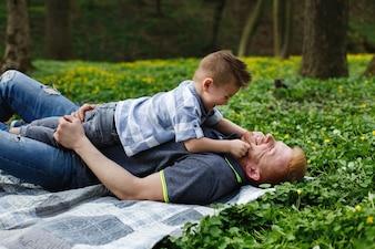 Alegre pai e filho se divertir jogando na manta em um parque verde