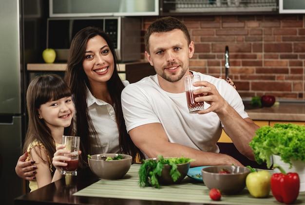 Alegre pai, mãe e filha tomando café juntos na cozinha