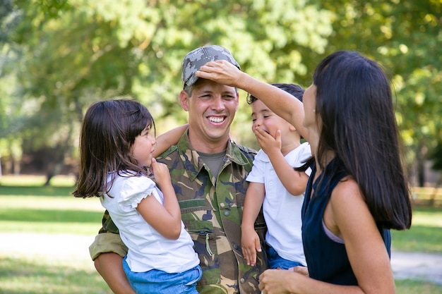 Alegre pai militar uniformizado, voltando para a família, segurando duas crianças nos braços. mulher ajustando o boné de maridos. conceito de reunião familiar ou retorno a casa