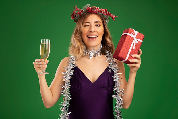 Alegre piscou jovem linda com vestido roxo e grinalda com guirlanda no pescoço segurando uma taça de champanhe com uma caixa de presente isolada no fundo verde