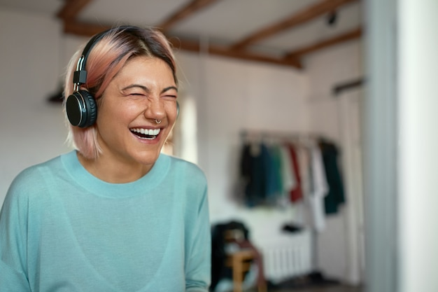 Alegre positiva jovem blogueira com argola no nariz, rindo durante a gravação de podcast, usando fone de ouvido.