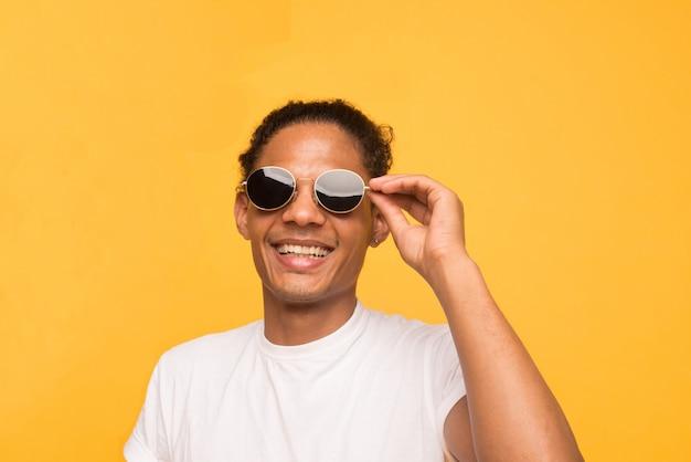 Alegre rapaz negro de camiseta branca e óculos de sol