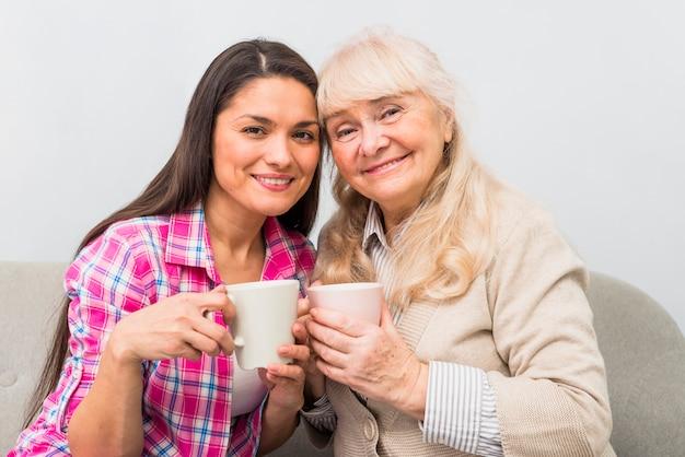 Alegre retrato de mãe e filha adulta segurando a caneca de café na mão