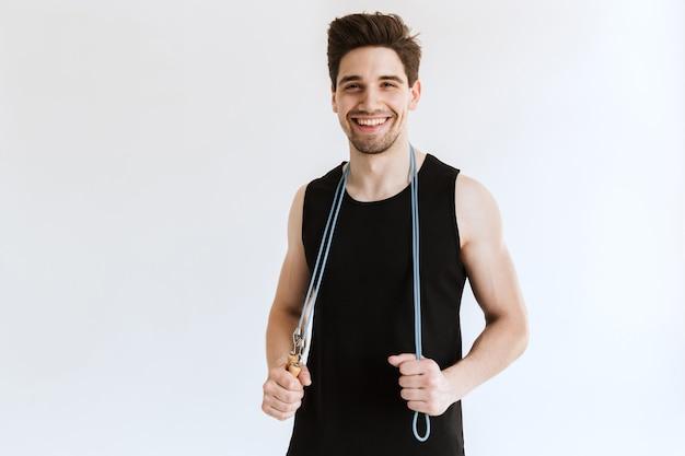Alegre satisfeito jovem esportes fortes homem posando e segurando a corda de pular.