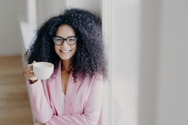 Alegre senhora afro-americana de cabelos encaracolados tem coffee-break, detém branco copo de bebida