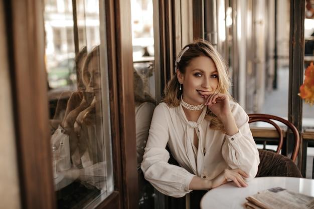 Alegre senhora atraente na blusa branca e joias de pérolas senta-se no café de rua. jovem loira com uma camisa vintage clara posa em um restaurante