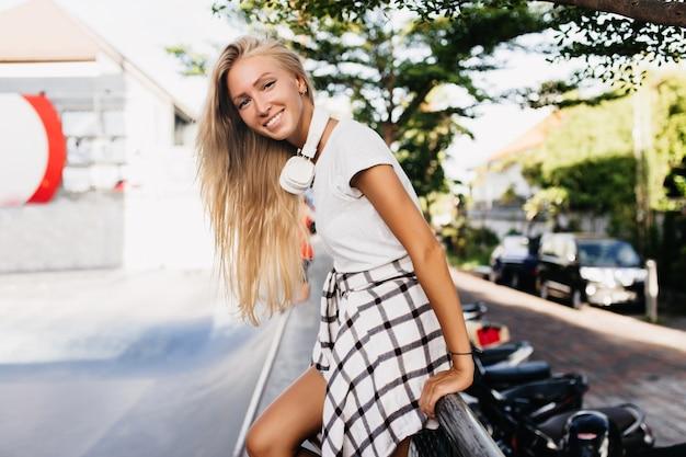 Alegre senhora caucasiana de camisa quadriculada, se divertindo perto da estrada num dia de verão.