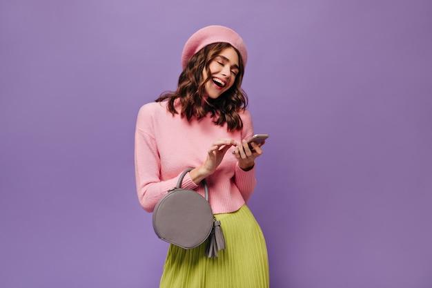Alegre senhora encaracolada de saia verde e boina rosa ri e segura o smartphone