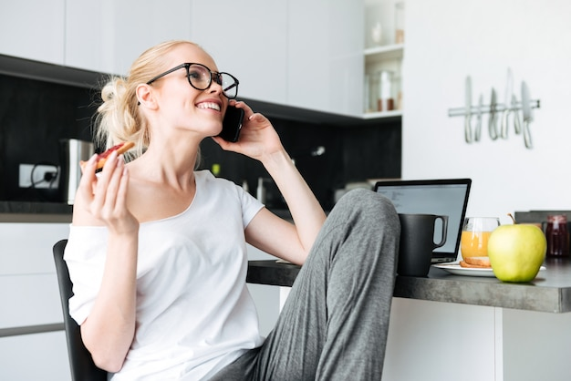 Alegre senhora rindo enquanto fala no smartphone na cozinha