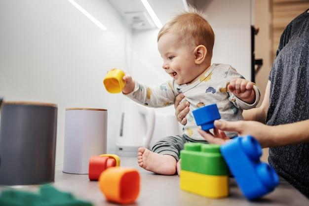 Alegre sorridente adorável garotinho sentado no balcão da cozinha e brincando com blocos de construção com sua mãe.