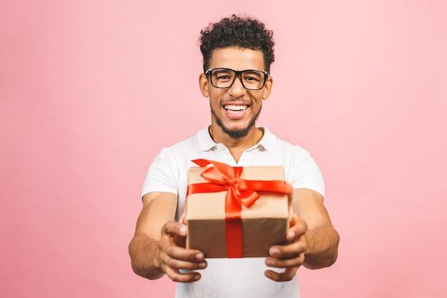 Alegre sorridente cara afro-americana de óculos segurando uma caixa de presente embrulhada