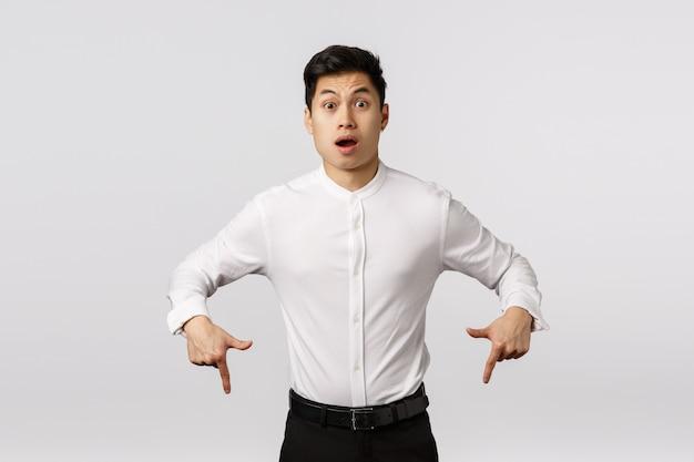 Alegre sorridente jovem empresário asiático com camisa branca, apontando para baixo