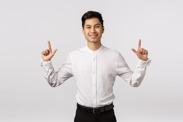 Alegre sorridente jovem empresário asiático com camisa branca apontando para cima