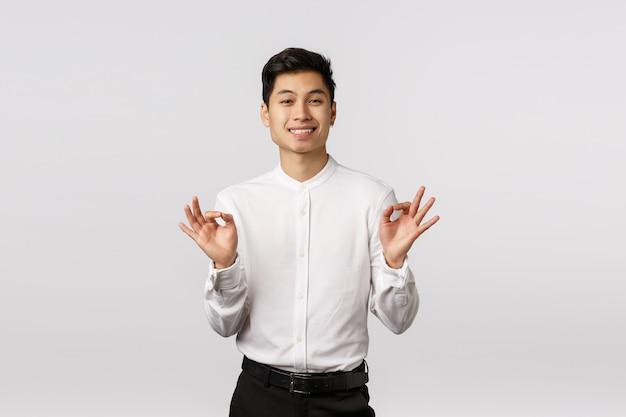 Alegre sorridente jovem empresário asiático com camisa branca com gesto bem com ambas as mãos