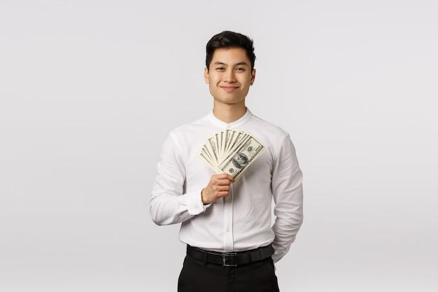 Alegre sorridente jovem empresário asiático com camisa branca, segurando as notas