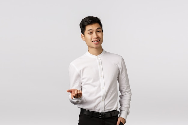 Alegre sorridente jovem empresário asiático com camisa branca sorrindo