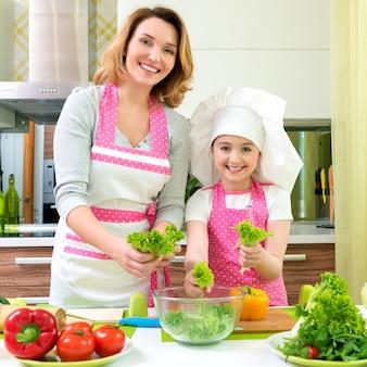 Alegre sorridente mãe e filha cozinhando uma salada na cozinha.