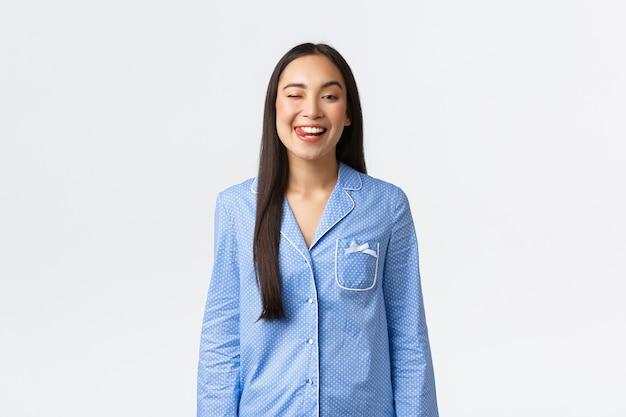 Alegre sorridente menina asiática de pijama azul, parecendo otimista, indo dormir. escovar os dentes e piscar satisfeito, preparando-se para a cama, em pé fundo branco satisfeito e feliz.