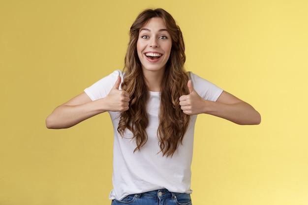 Alegre suportivo energizado fofo europeu fofo menina de cabelos encaracolados mostrar aprovação positiva torcendo pelo amigo excelente esforço acenando com a cabeça aceitando um ótimo trabalho incrível feito fundo amarelo