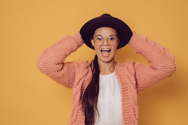 Alegre surpresa morena de óculos, vestido de suéter roxo, segurando seu chapéu com a boca aberta, gritando. conceito de pessoas felizes.