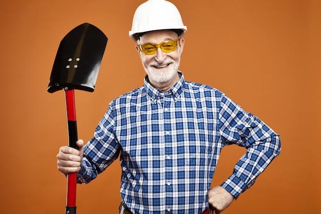 Alegre trabalhador da construção civil na aposentadoria usando capacete protetor e óculos amarelos, usando uma pá para cavar, posando isolado contra a parede em branco do copyspace