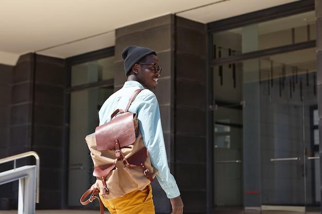 Alegre turista masculino de pele escura bonito com mochila, vestindo roupas da moda prestes a entrar no edifício moderno da embaixada para estender o visto enquanto passa as férias de verão no país estrangeiro
