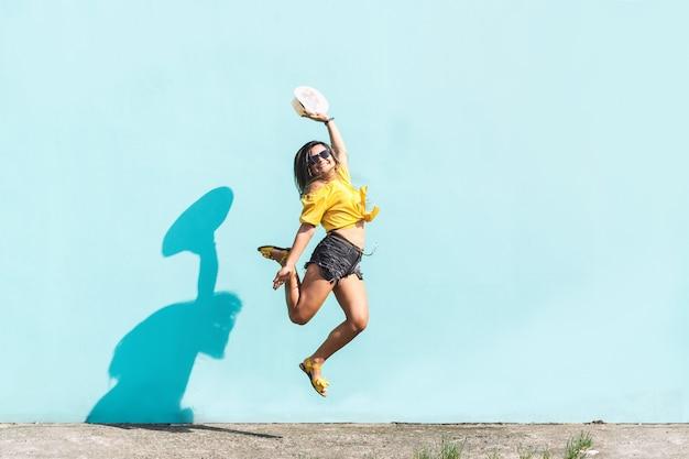 Alegrel jovem latino-americana pulando de felicidade no conceito urbano de rua