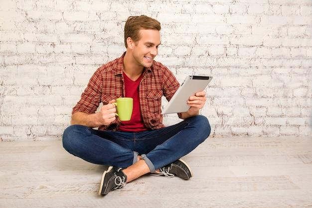 Alegremente mandrando chá e lendo notícias no tablet
