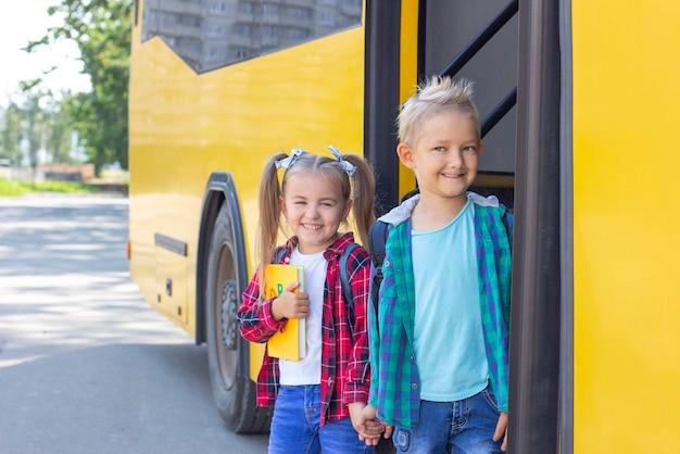 Alegres alunos com mochilas descem do ônibus escolar.