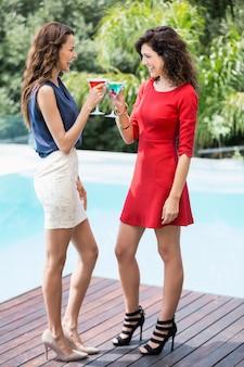 Alegres amigas brindando cocktails