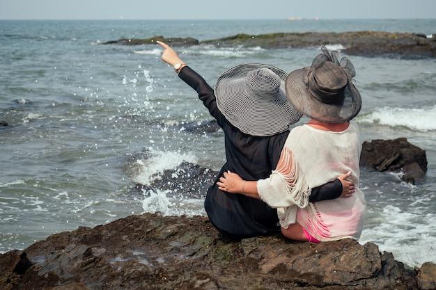 Alegres amigas na praia, sente-se em chapéus