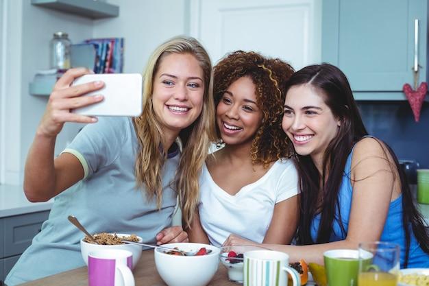 Alegres amigas tomando selfie