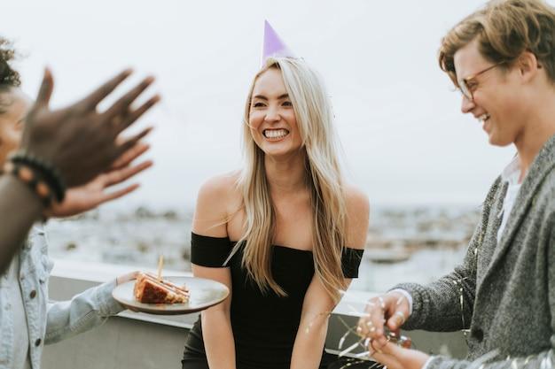 Alegres amigos comemorando uma festa de aniversário em um telhado