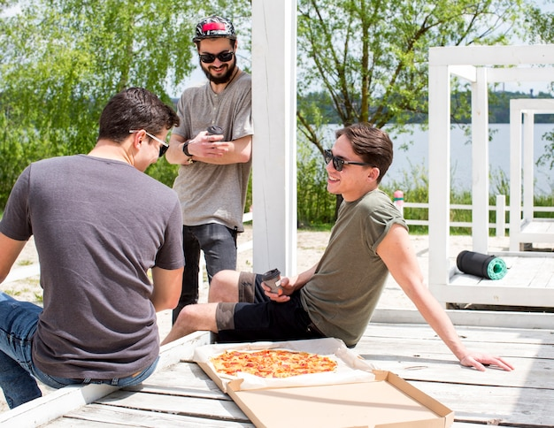Alegres amigos conversando no piquenique pelo lago