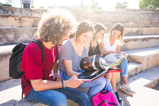 Alegres amigos estudando nas escadas da rua