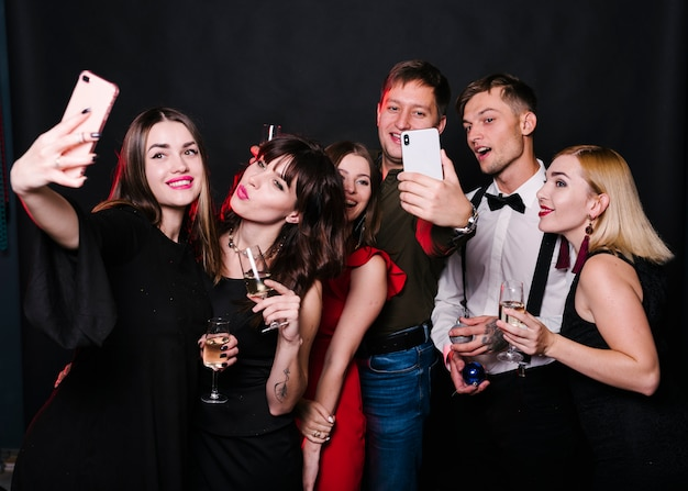 Alegres amigos fazendo selfie com vinho espumante