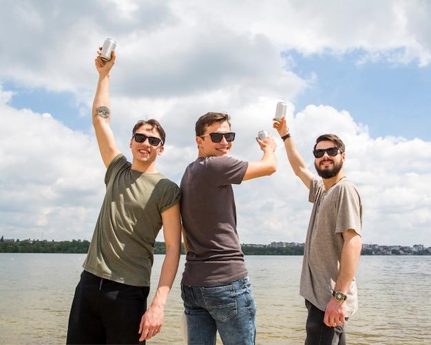 Alegres amigos levantando as mãos com cerveja
