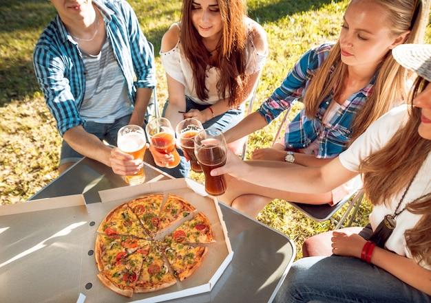 Alegres amigos no piquenique no parque. comendo pizza