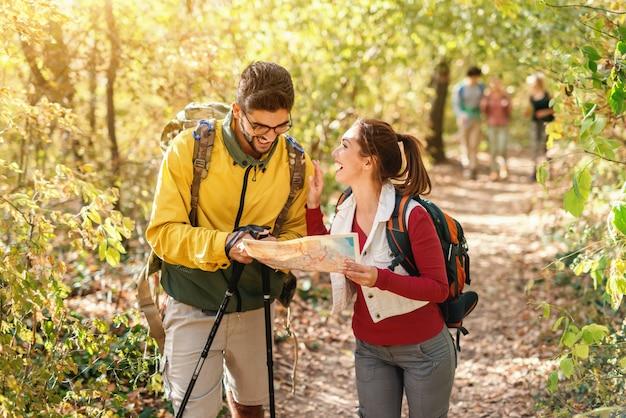 Alegres caminhantes olhando o mapa e procurando o caminho certo. tempo de outono no exterior da floresta.