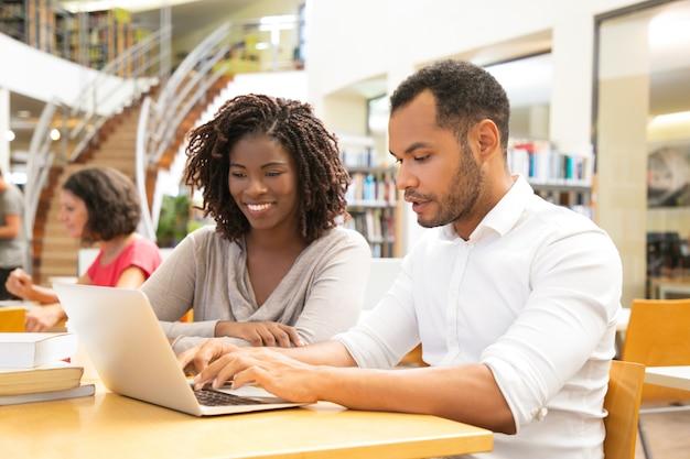 Alegres colegas sentado na biblioteca e se comunicar
