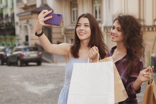 Alegres compradores femininos usando telefone inteligente, tirando fotos depois das compras