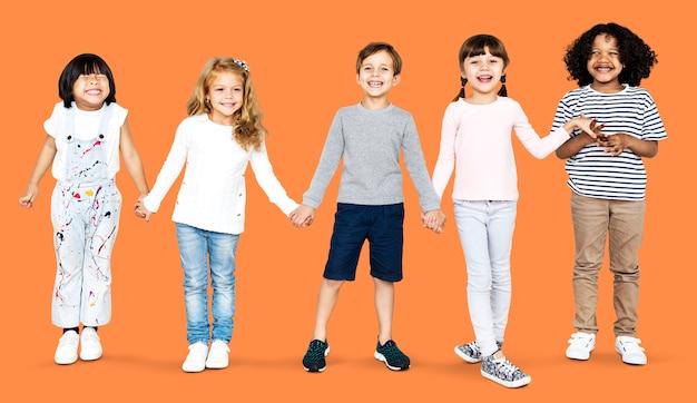 Alegres crianças de mãos dadas