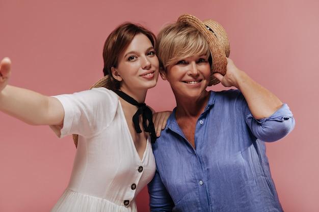 Alegres duas mulheres com penteado curto legal e chapéu de palha em vestidos da moda, sorrindo e tomando selfie no fundo rosa.